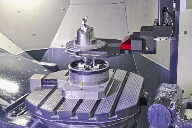 Bras de robot qui positionne la palette sur le référentiel de centrage  Erowa installé sur une machine d'usinage.